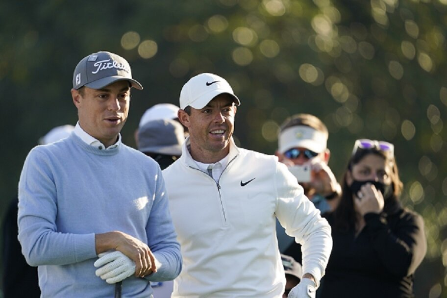 Justin Thomas and Rory McIlroy wait for their golf shots